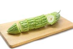 Le melon amer ou la courge amère a découpé le ‹en tranches d'†de ‹d'†sur les planches à découper en bois sur le fond blanc Image libre de droits