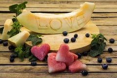Le melon est découpé l'amour de mot Images stock
