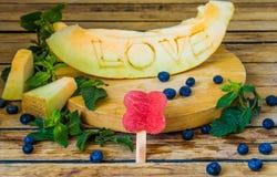 Le melon est découpé l'amour de mot Photos stock
