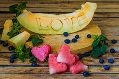 Le melon est découpé l'amour de mot Photos libres de droits