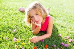 Le mensonge blond de fille d'enfant a détendu dans l'herbe de jardin avec des fleurs Photos stock