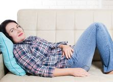 Le mensonge de sourire de femme tranquille sereine d'une cinquantaine d'années sur la fille de pièce de divan à la maison a la co image stock