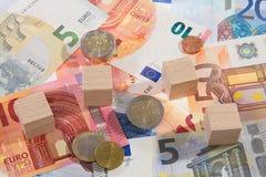 Le mensonge des billets de banque avec en bois découpe des pièces de monnaie Image stock