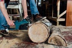 Le menuisier dans l'atelier scie l'arbre avec une tronçonneuse électrique charpentier en cours de sawing Photographie stock libre de droits