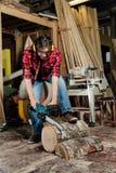 Le menuisier dans l'atelier scie l'arbre avec une tronçonneuse électrique charpentier en cours de sawing photo stock