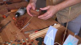 Le menuisier doué décore son petit bateau en bois banque de vidéos