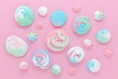 Le meringhe nei colori pastelli, modellano l'estratto su fondo rosa Fotografia Stock Libera da Diritti