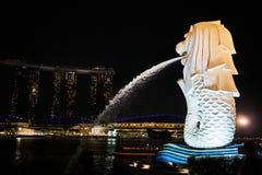 Le Merlion de Singapour répandant un courant d'eau dans la rivière la nuit image stock