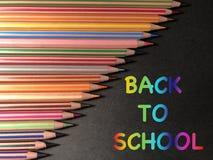 Le message ce coloré DE NOUVEAU À L'ÉCOLE sur le fond noir photos stock