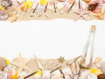 Le message dans une bouteille en verre se trouve sur la plage de sable avec des coquillages et des étoiles de mer images libres de droits