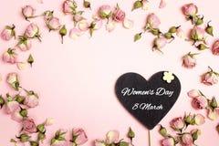 Le message de salutation de jour du ` s de femmes sur le coeur-tableau noir avec petit sèchent images stock