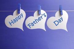 Le message heureux de jour de pères écrit sur la forme blanche de coeur étiquette pendre des chevilles bleues sur une ligne Photo libre de droits