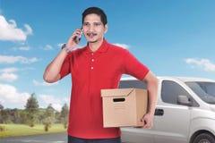 Le messager masculin asiatique beau avec le téléphone apportent le colis photographie stock libre de droits