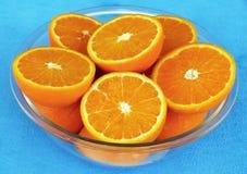 Le metà delle arance in ciotola di vetro sulla tavola blu coprono Fotografie Stock