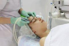 Le meulage de la peau du visage est fait par un cosmetologist dans un salon de beauté photographie stock libre de droits