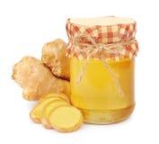 Le miel dans des chocs en verre et un gingembre s'enracinent images stock
