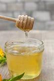 Le miel de tilleul dans le pot et le calendula fleurit sur la table en bois Photo stock