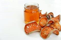 Le miel et le bael sec portent des fruits sur le fond blanc Image libre de droits