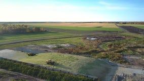 Le mietitrici di insilamento di vista aerea tamp il pozzo del silo vicino all'azienda agricola stock footage