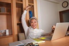 Le milieu attrayant heureux et r?ussi a vieilli la femme asiatique travaillant ? la c?l?bration excit?e et gaie de bureau d'ordin photo libre de droits