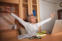 Le milieu attrayant heureux et r?ussi a vieilli la femme asiatique travaillant ? la c?l?bration excit?e et gaie de bureau d'ordin photos libres de droits
