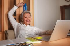 Le milieu attrayant heureux et r?ussi a vieilli la femme asiatique travaillant ? la c?l?bration excit?e et gaie de bureau d'ordin photos stock