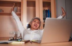 Le milieu attrayant heureux et r?ussi a vieilli la femme asiatique travaillant ? la c?l?bration excit?e et gaie de bureau d'ordin image libre de droits