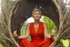 Le milieu attrayant 40s ou 50s et heureux a vieilli la femme asiatique dans la relaxation de pratique de yoga de robe rouge chiqu image libre de droits
