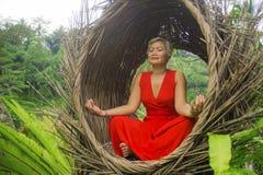 Le milieu attrayant 40s ou 50s et heureux a vieilli la femme asiatique dans la relaxation de pratique de yoga de robe rouge chiqu photographie stock