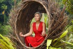 Le milieu attrayant 40s ou 50s et heureux a vieilli la femme asiatique dans la relaxation de pratique de yoga de robe rouge chiqu photographie stock libre de droits