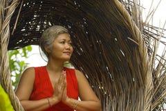 Le milieu attrayant 40s ou 50s et heureux a vieilli la femme asiatique dans la relaxation de pratique de yoga de robe rouge chiqu photo libre de droits