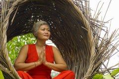 Le milieu attrayant 40s ou 50s et heureux a vieilli la femme asiatique dans la relaxation de pratique de yoga de robe rouge chiqu photos libres de droits