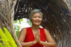Le milieu attrayant 40s ou 50s et heureux a vieilli la femme asiatique dans la relaxation de pratique de yoga de robe rouge chiqu images stock