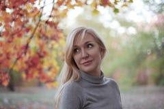 Le milieu attrayant a vieilli la femme caucasienne avec les yeux verts au parc d'automne, souriant, seulement tenue de détente Co image libre de droits