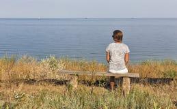 Le milieu blanc a vieilli la femme s'asseyant sur le banc en bois avec le paysage marin Image libre de droits