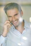 Le milieu de sourire a vieilli l'homme d'affaires à un téléphone, regardant par la fenêtre Photo stock