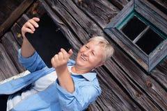 Le milieu de sourire a vieilli la femme regardant et riant de son t numérique Photos stock