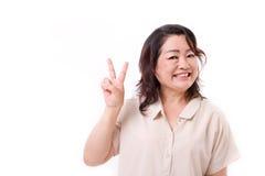 Le milieu heureux et sûr a vieilli la femme se dirigeant vers le haut du signe de v, victoire Photos stock