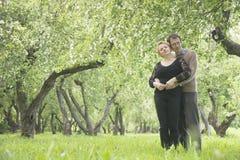 Le milieu heureux a vieilli des couples dans le jardin de pommiers photo stock