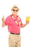 Le milieu heureux a vieilli l'homme des vacances tenant un cocktail et un givin Photos stock