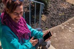 Le milieu heureux a vieilli la femme caucasienne souriant et recherchant de son téléphone portable Le téléphone indique le gagnan photo stock