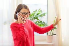 Le milieu heureux a vieilli parler femelle de femme au téléphone portable mobile Fenêtre de fond dans la maison photos stock