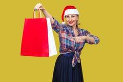 Le milieu moderne heureux a vieilli la femme dans le chapeau rouge de Santa et SH à carreaux photographie stock libre de droits
