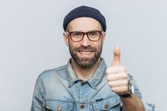 Le milieu positif a vieilli le mâle avec la barbe épaisse et la moustache, montre o photo libre de droits