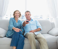 Le milieu satisfait a vieilli des couples se reposant sur le divan regardant la TV Images stock