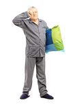 Le milieu somnolent a vieilli l'homme dans des pyjamas tenant un oreiller Image stock