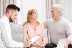 Le milieu a vieilli le contrat de signature de couples se reposant sur le divan Images libres de droits