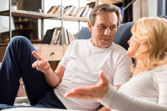 Le milieu a vieilli des couples parlant et se trouvant sur le lit à la maison photo stock