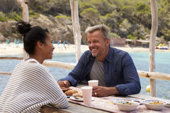 Le milieu a vieilli des couples se reposant à la table par la mer regardant loin Images stock