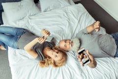 Le milieu a vieilli des couples se situant dans le lit avec des smartphones Photographie stock